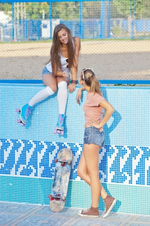 two beautiful young girls in an empty pool, one wearing roller scates, the other - with a scateboard photo