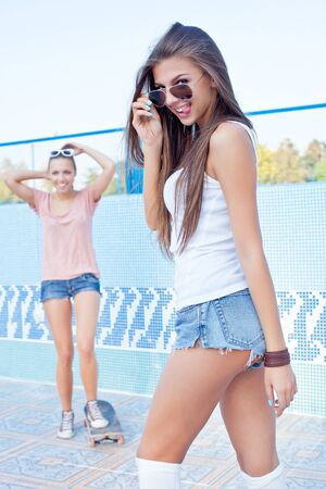 a beautiful young girl is watching the other flirting and setting the sunglasses photo