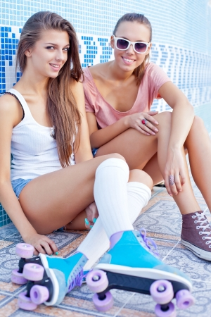 two beautiful young girls on the floor of an empty pool smiling for the camera