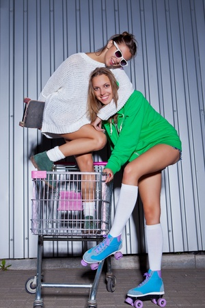 a girl in sunglasses holding a scateboard is hugging a girl in a green hoodie and roller scates