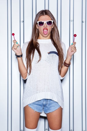 a beautiful young gir in sexy shorts holds two red lollipops and puts out her tongue  Stock Photo