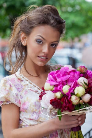 a beautiful young brunette girl in summer dress with a bunch of flowers is looking into the camer