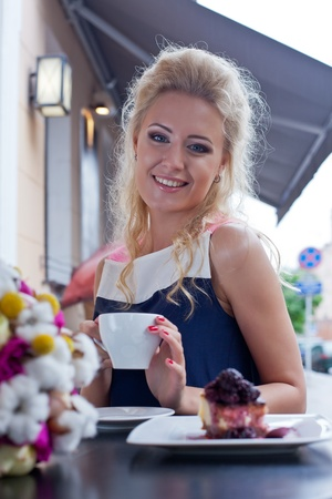 a beautiful young blond girl in summer dress at the table in pavement cafe is smiling for the camera  Stock Photo