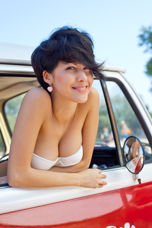 a beautiful sun tanned young girl with short hair cut and blue eyes is smiling for the camera Stock Photo