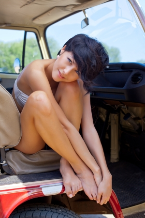 a sun tanned young girl with short hair cut and blue eyes in the front seat is embracing her long beautiful legs