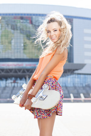 young beautiful girl wearing flower skirt and orange top holding a skateboard smiles for the camera photo
