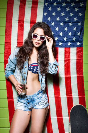 beautiful sexy long haired girl with glass bottle of water and skateboard against american flag sets sunglasses photo