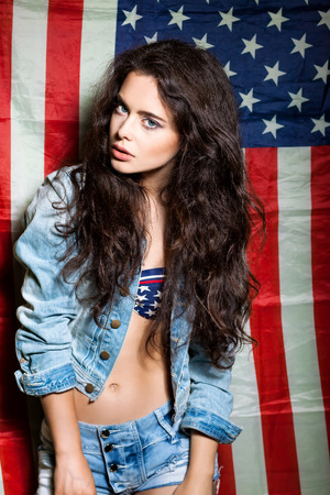 beautiful long haired posh girl  against usa flag poses for the camera photo