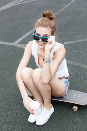 beautiful smiling girl with a white to-go cup looking over sunglasses sits on skateboard at basketball court