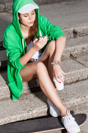 beautiful young girl in green hoodie chats on cellphone sitting on stone stairs with her legs on skateboard Stock Photo