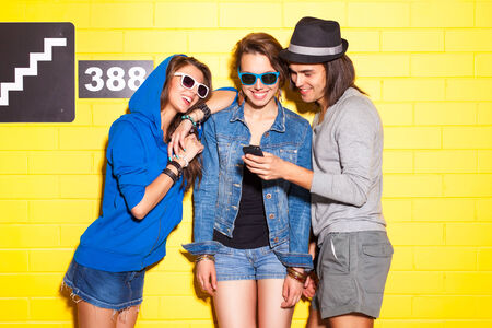 handsome boy in hat shows his cellphone to two beautiful young girls in sunglasses in front of yellow brick wall