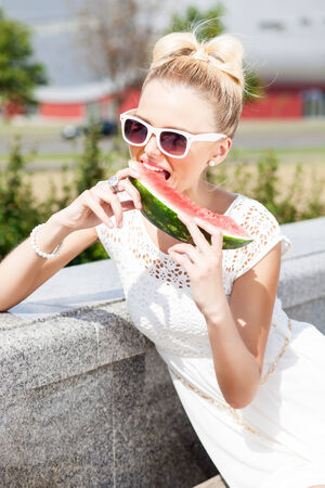 young blonde girl in white summer dress wearing sunglasses bites juicy watermelon photo
