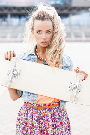 young beautiful girl wearing flower skirt holds a skateboard with blank deck photo