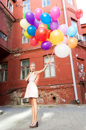 beautiful surprised girl in pink dress holding a bunch of balloons in front of old wall
