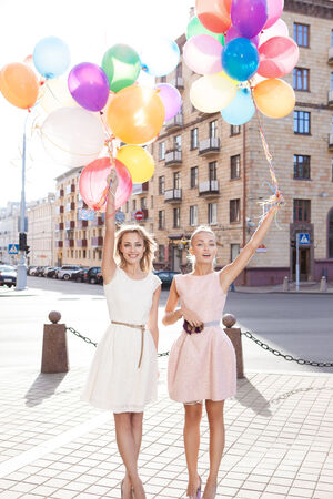 two smiling girls in white and pink dresses holding bunches of multicolored balloons in sun in the city street photo