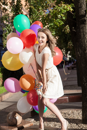 beautiful happy girl in summer dress with a bunch of multicolored balloons on the bench