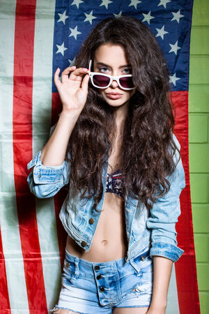 beautiful long haired girl in sunglasses against usa flag poses for the camera photo