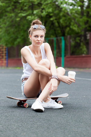 beautiful young girl in jeans shorts sits on skateboard at basketball court holding a to-go cup Stock Photo
