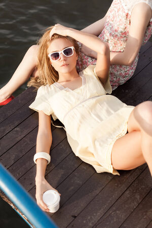 beautiful tanned girl in yellow summer dress with a to-go cup lies on her girlfriend Stock Photo