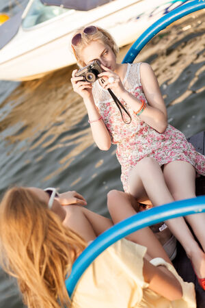 beautiful blonde girl in flower dress with photo camera takes picture of her tanned ginger girlfriend at sunset Stock Photo