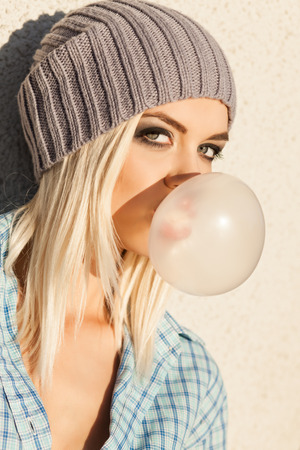 Close-up of beautiful young blond girl in beanie hat blows big bubble from bubble gum Stock Photo