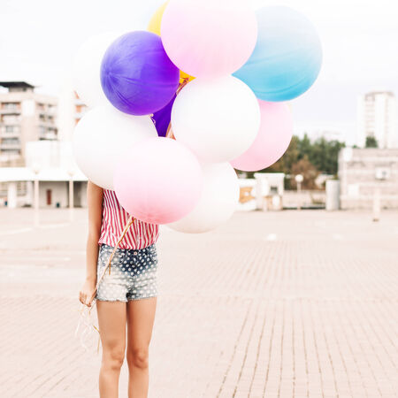 girl in short jeans shorts, sleeveless striped top and high heels stands in bunch of balloons