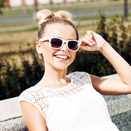 girl in red dress: young girl in white summer dress wearing sunglasses smiles for the camera