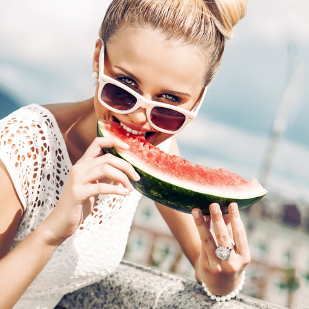 beautiful young girl with bow tie hair in white summer dress wearing sunglasses bites juicy watermelon Фото со стока