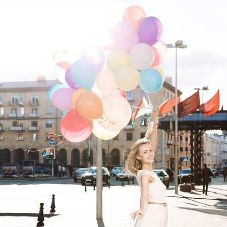 beautiful blonde girl with long legs in summer dress holds a bunch of multicolored balloons