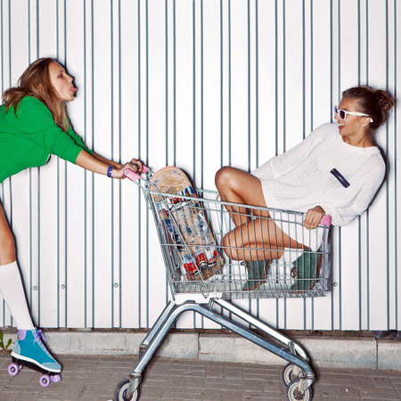 a beautiful young girl in sexy shorts, stockings and roller skates is showing out her tongue to a beautiful girl in a supermarket trolley  photo