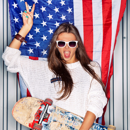 Beautiful girl with a skateboard in front of a flag of the U. S. Stock Photo