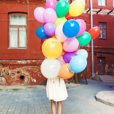 birthday adult: girl in white summer dress hides herself behind a bunch of balloons Stock Photo