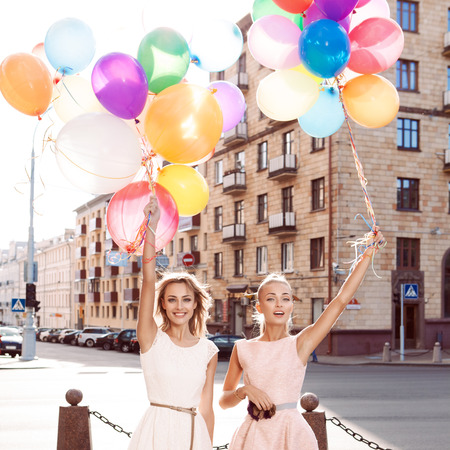 two smiling girls in white and pink dresses holding bunches of multicolored balloons in sun in the city street