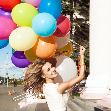 portrait of beautiful blonde girl with a bunch of multicolored balloons in summer sunny day at stairs of building