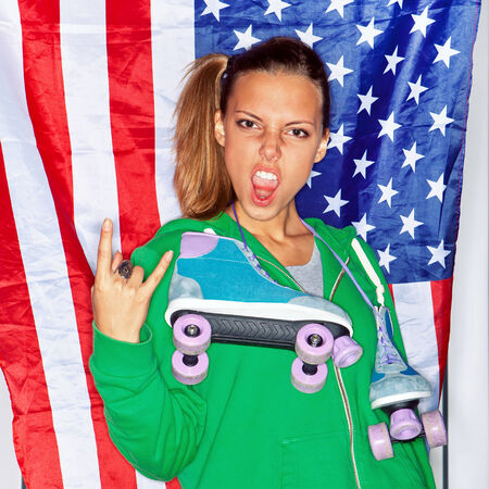 u.s. flag: Beautiful girl with a roller skates in front of a flag of the U. S.