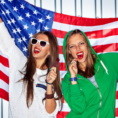 Two beautiful girls with red lollipops holding a flag of the USA 免版税图像 - 30751672