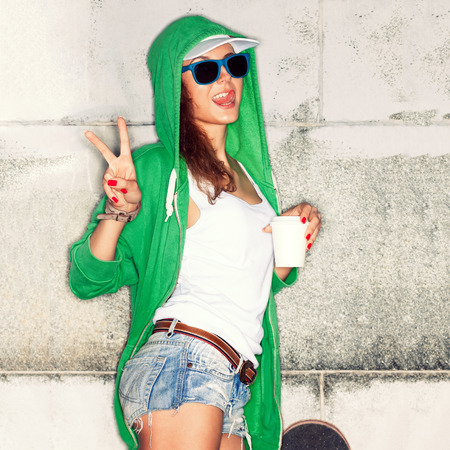 beautiful young girl in green hoodie and blue sunglasses with white to-go cup shows victory sign against grey wall