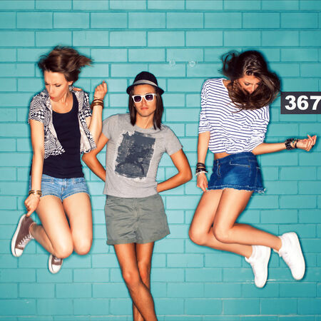 girls jump playing air invisible guitar while boy in hat and sunglasses poses for the camera in front of blue brick wall