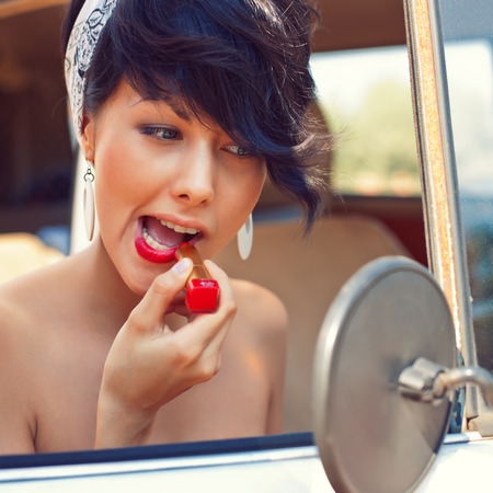 a beautiful young girl with short hair cut and blue eyes is looking into the side view mirror and is putting on red lipstick photo