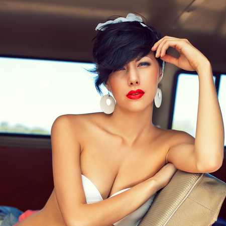 a beautiful retro-looking girl with blue eyes and red lips sitting on the backseat of the car in sexy jeans shorts is looking into the camera