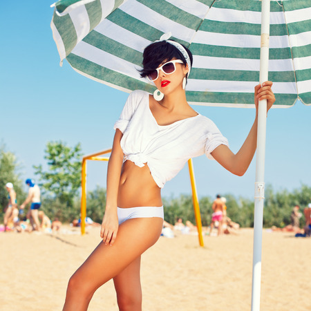 a beautiful young girl in retro look with red lips in a white swimsuit, a bandana and sunglasses is standing under the beach umbrella and is posing for the camera
