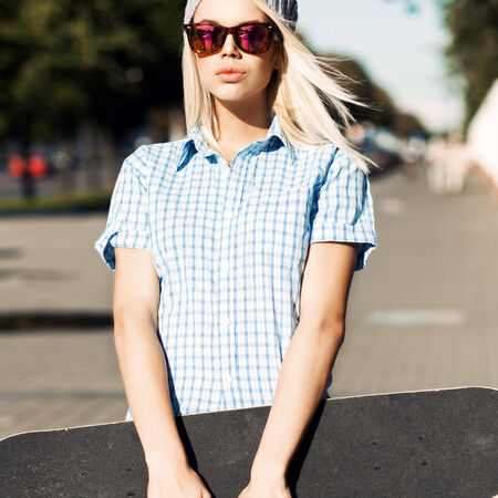 Young blond girl with plump lips in sunglasses stands in the street on sunny day holding skateboard with two hands Stock Photo