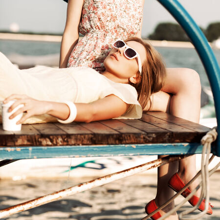beautiful tanned girl in yellow summer dress with a to-go cup sleeps on her girlfriends knee on wooden bridge under water