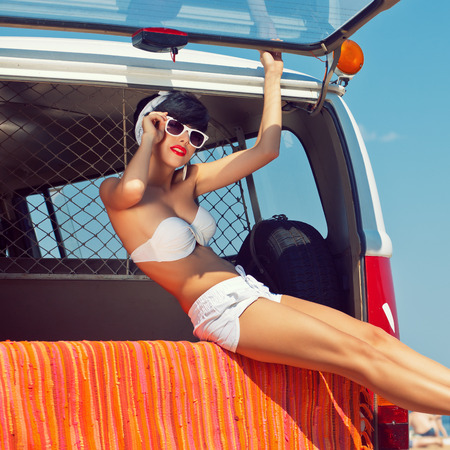 bandana girl: a beautiful young girl in retro look with a white swimsuit, a bandana, sunglasses and flip flops is sitting in the car trunk