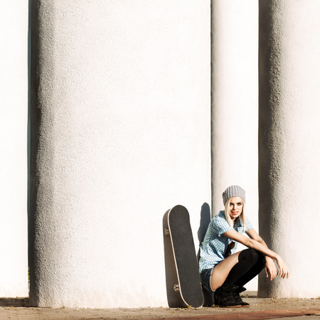 Beautiful girl in short shorts and stockings with skateboard sits on her haunches near  columns on sunny day Stock Photo