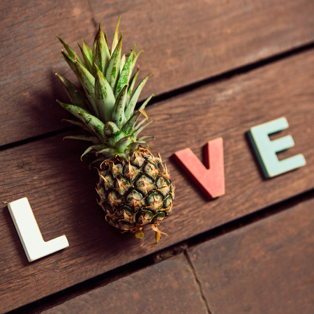 word love made up of colorful wooden letters with pineapple instead of letter O on the wooden floor. February 14, Valentine