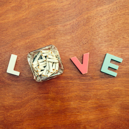 word love made up of colorful wooden letters with dirty ashtray full of butts instead of letter O on a wooden board. February 14, Valentine photo