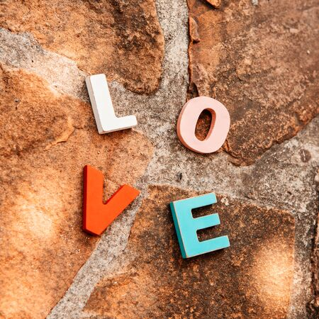 word love made up of colorful wooden letters on a stone floor, view from the top. February 14, Valentine photo