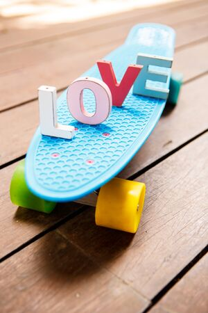 word love made up of colorful wooden letters on the blue pennyboard longboard. February 14, Valentine