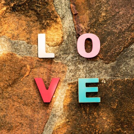 word love made up of colorful wooden letters on a stone floor, top view. February 14, Valentine photo